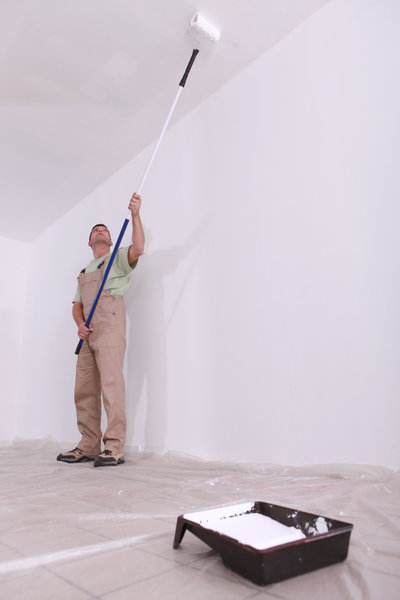 worker painting ceiling home white