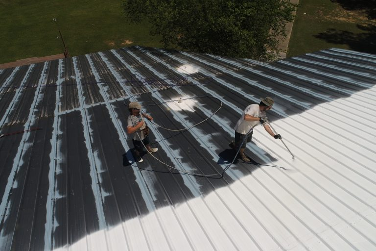 commercial painting, spraying white paint on roof
